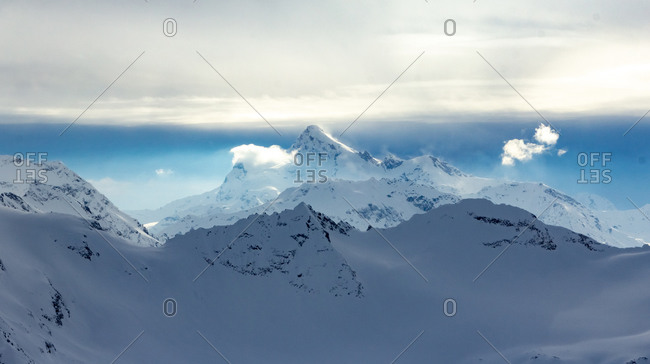 Snowy Mountains in blue and white sky
