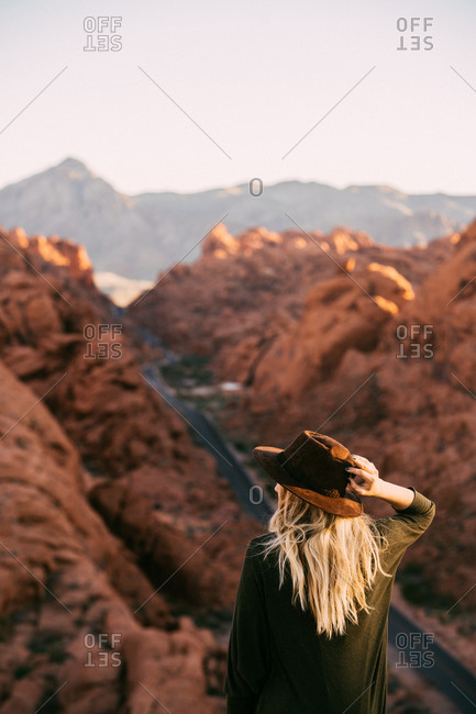 Young girl looking at the magnificent landscape while holding her hat