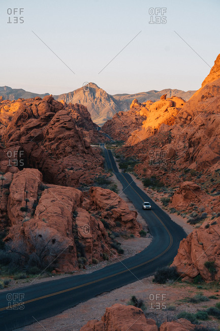 Car driving on a road trough a valley surrounded by red rocks