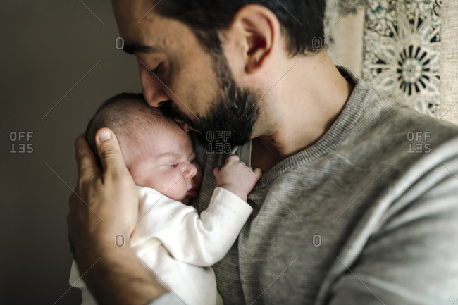 Bearded dad lovingly kisses head of sleeping newborn in his arms