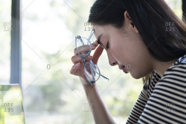 Tired woman holding glasses touching her forehead