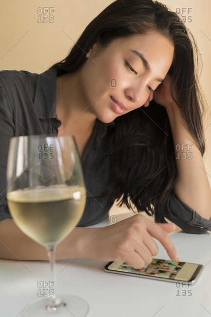 Woman using smart phone next to glass of wine