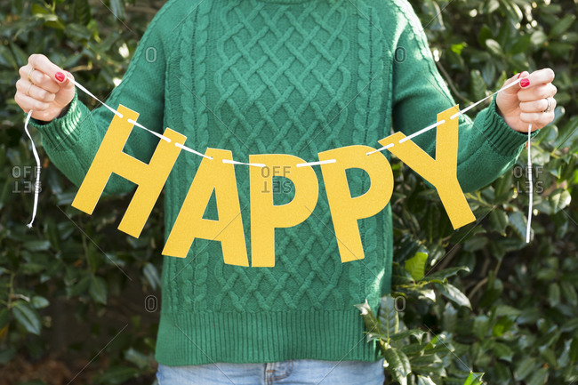 Woman holding 'happy' letters on string