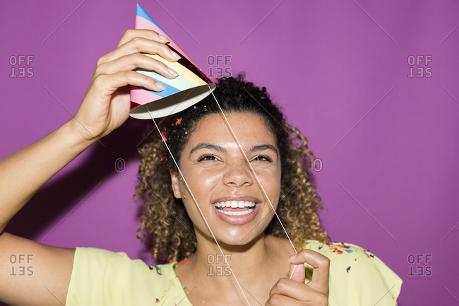Smiling woman putting on party hat