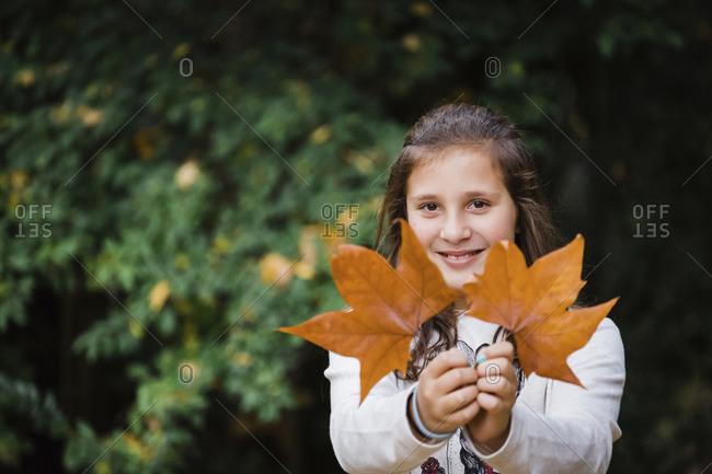 Smiling girl holding autumn leaves