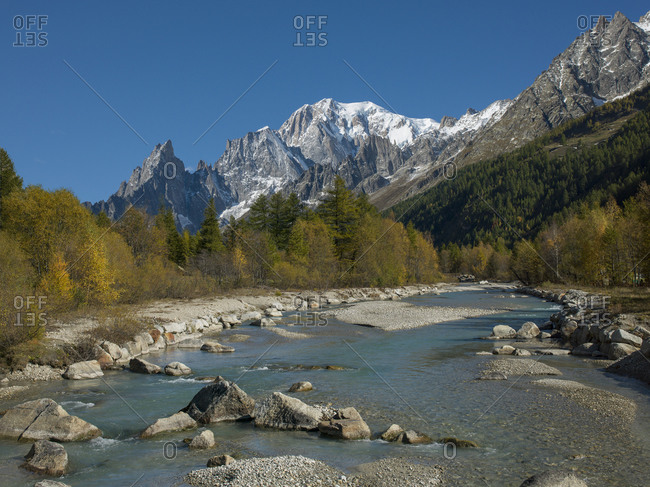 Snowcapped mountain by river in Aosta Valley, Italy