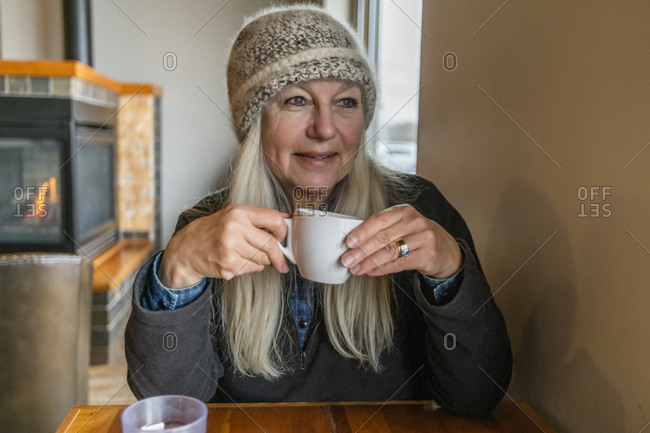 Woman wearing winter clothing holding cup