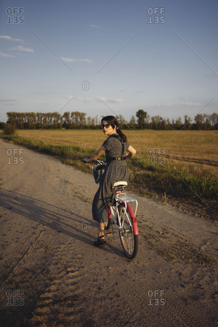 Woman riding bicycle on country road