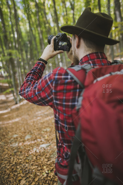 Man taking photograph in forest