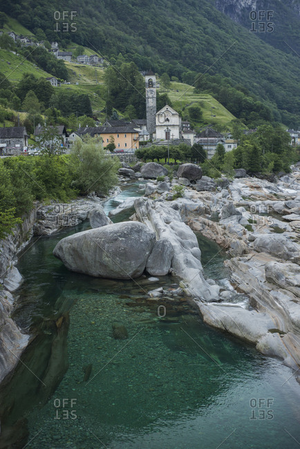 Bell tower by river in Ticino, Switzerland