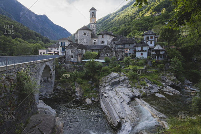 Bell tower by bridge and river in Ticino, Switzerland