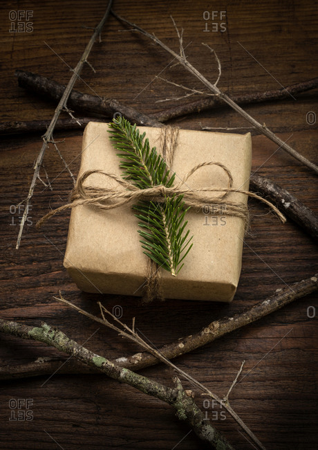 Pine frond tied to Christmas present next to sticks