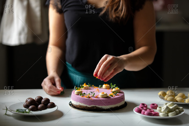 Confectioner decorates a raw foodism pie with berries for vegans