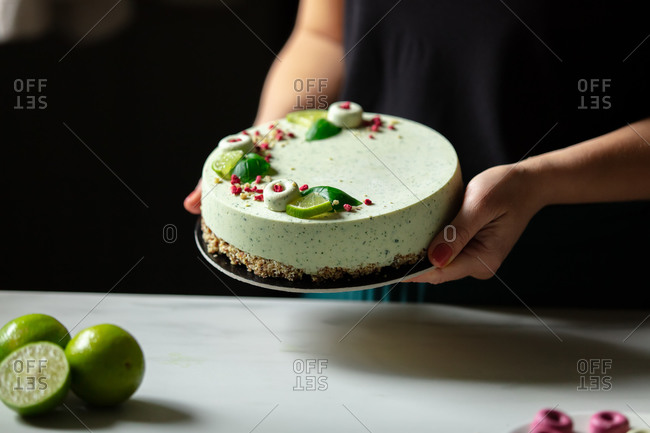 Confectioner decorates a raw foodism pie with lime for vegans