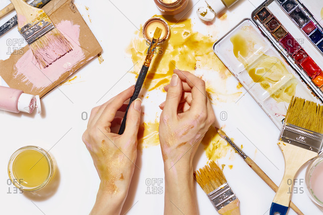 Overhead image of artist's table with paper and utensils. Workspace of designer illustrator. Female hands covered with paint holding a brush