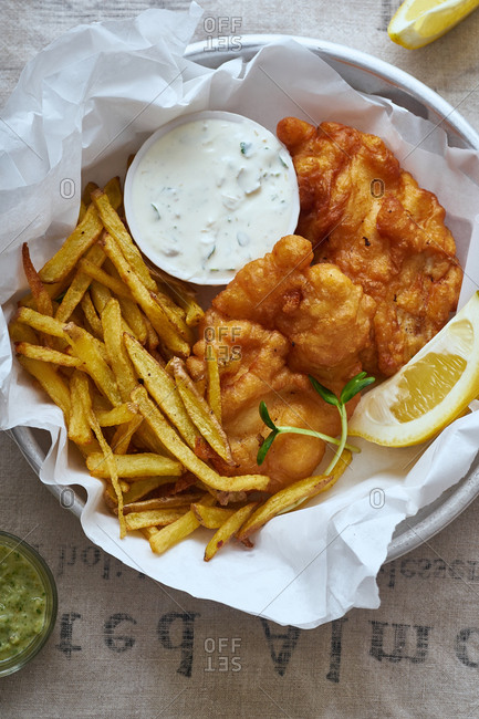 Fish and chips with beer, lemon slices and sauce on linen tablecloth