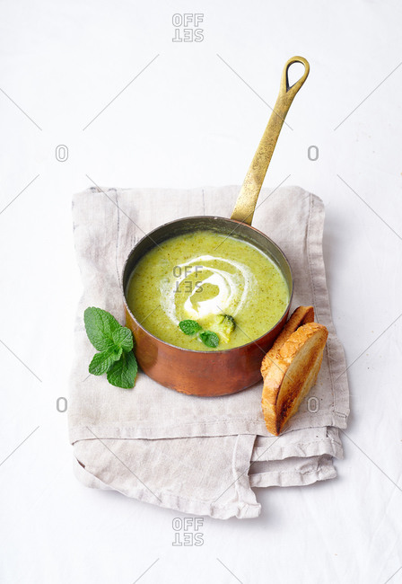 Broccoli soup with mint in copper pot with toasted bread