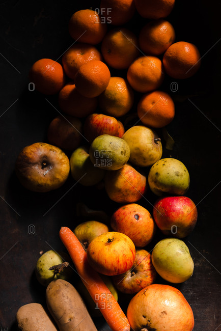 From above fresh juicy apples tangerine with pomegranate and orange carrot on black surface in light