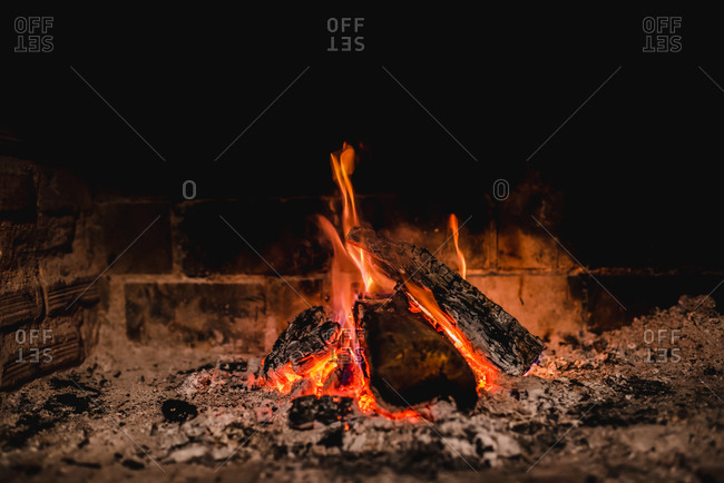Yellow flames rising up from bonfire on wooden pieces in nature at night