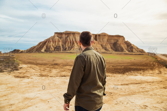 Back view of anonymous man traveler in casual clothing standing looking at big mountain in brown cliff and blue sky on background in Bardenas Reales, Navarre, Spain