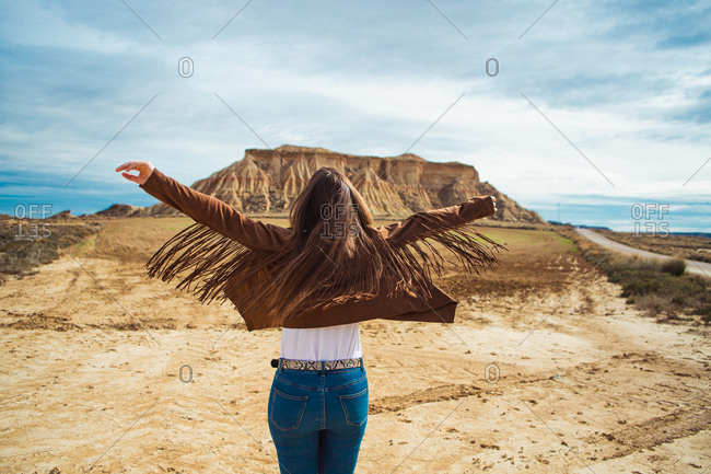 Back view of anonymous woman traveler in casual clothing standing with raised hands near brown cliff and blue sky on background in Bardenas Reales, Navarre, Spain