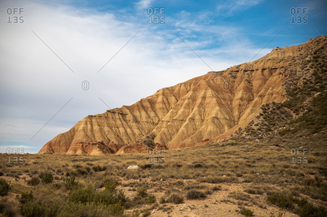 Empty field with green sparse vegetation and brown powerful cliff on background under cloudy blue sky in Bardenas Reales, Navarre, Spain