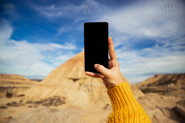 Crop female hands of anonymous traveler taking picture of big brown cliff with colorful blue sky and white clouds on background at Bardenas Reales at Spain