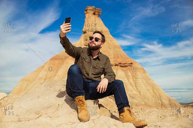 Content bearded male in casual wear and sunglasses using mobile phone while resting at foot of brown mountain with blue sky on background at Bardenas Reales