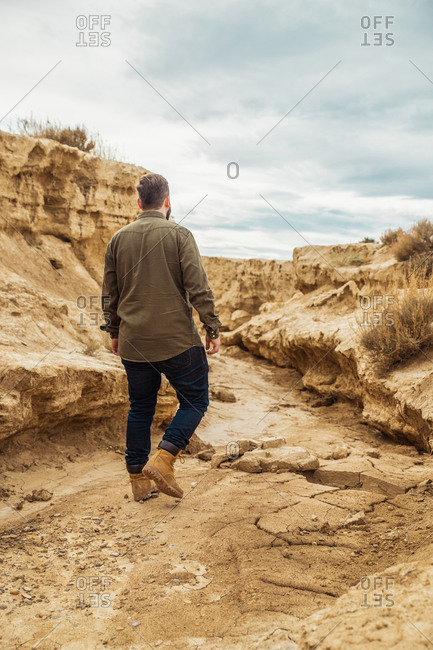 Back view of faceless male traveler in casual clothing in narrow passage between big brown stones in Bardenas Reales, Navarre, Spain