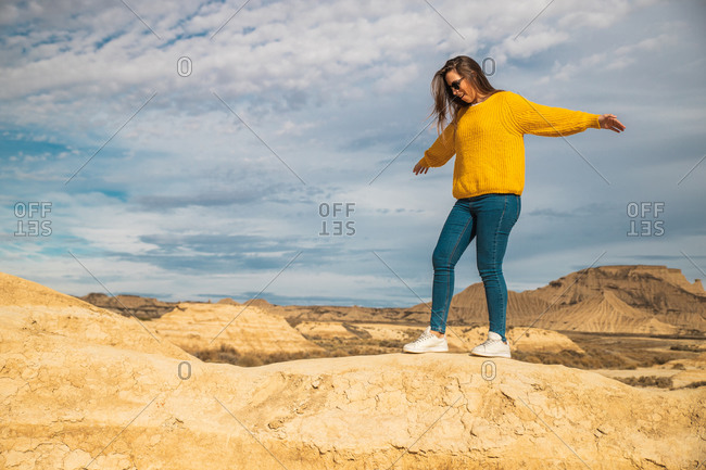 Side view of young female tourist in yellow sweater blue jeans and white sneakers spreading arms for balance while walking along peak of brown hill in Bardenas Reales, Navarre, Spain