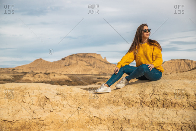 Joyful young female traveler in stylish casual wear sitting in brown hill with blue sky on background in Bardenas Reales, Navarre, Spain