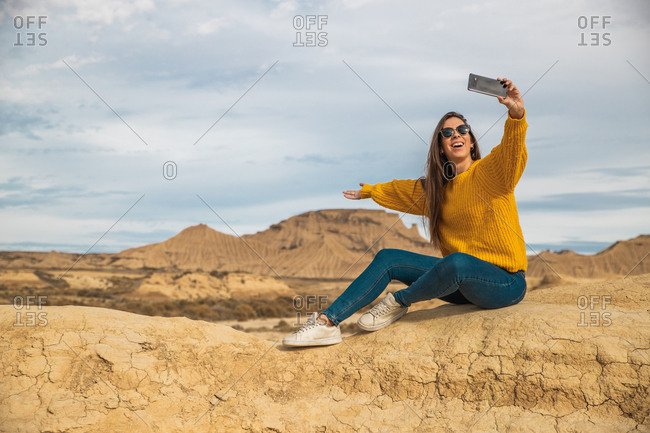 Joyful young female traveler in stylish casual wear smiling while taking selfie on mobile phone with brown hill and blue sky on background in Bardenas Reales, Navarre, Spain