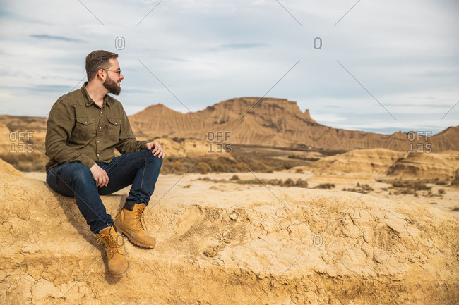 Low angle of content bearded male in casual wear and sunglasses smiling while resting at foot of brown mountain with blue sky on background at Bardenas Reales