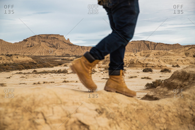 Legs on faceless traveler in brown boots and blue jeans standing on dirty sandy road with mountain and sky on blurred background in Bardenas Reales, Navarre, Spain