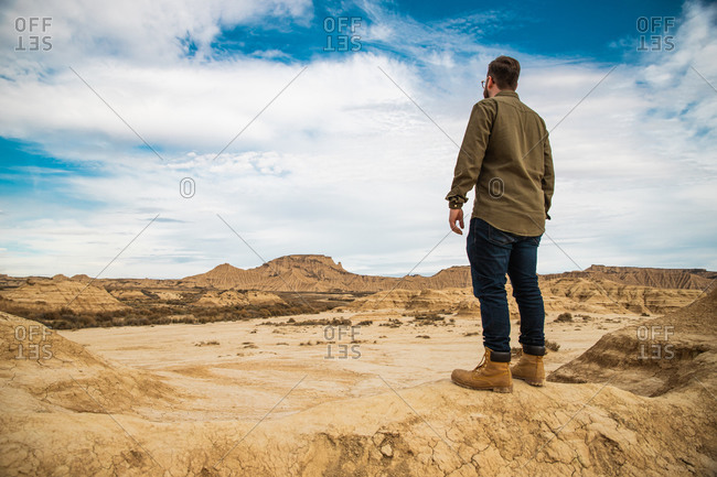 Back view of anonymous man in casual wear resting on brown mountain with blue sky on background at Bardenas Reales
