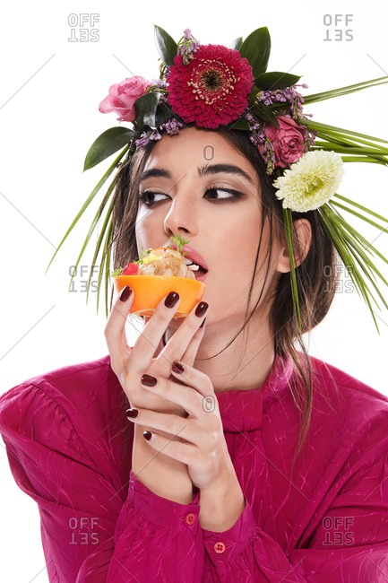 Young gorgeous woman with wreath of colorful flowers on head looking away while holding dish in orange zest isolated on white background