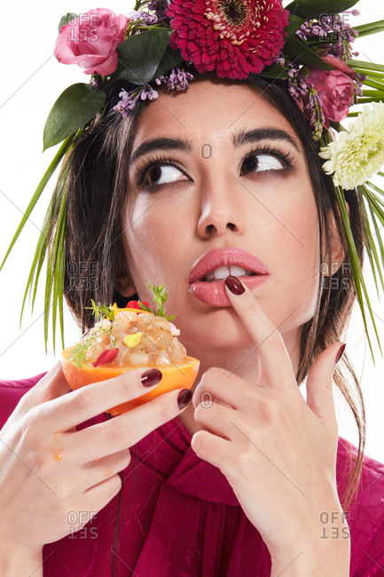 Young gorgeous woman with wreath of colorful flowers on head and finger on lip looking away while holding dish in orange zest isolated on white background