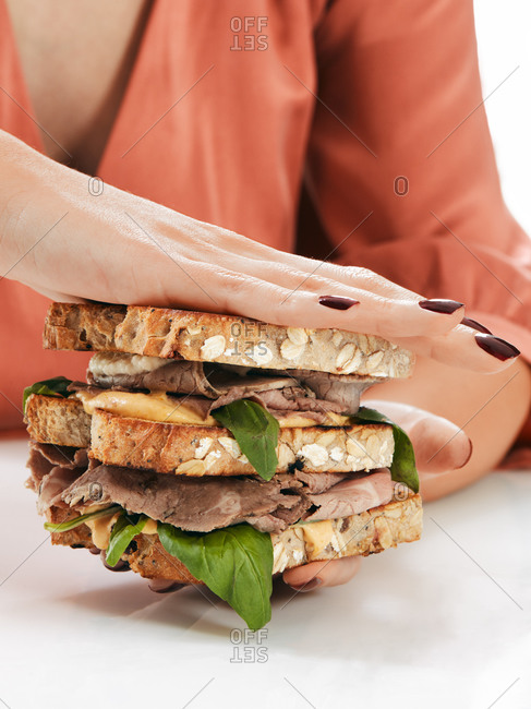 Crop hands of faceless woman holding in palms double sandwich with fresh greenery rye bread and meat