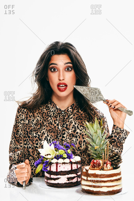 Surprised fashionable lady with trendy makeup holding pastry spatula and looking at camera while sitting at table with creatively decorated cakes isolated on white background