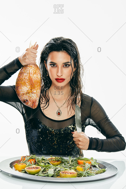 Stylish brunette with red lips holding knife and round fresh fish while looking at camera and sitting at table with tasty snacks