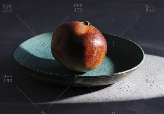 Blue plate with single ripe fresh pomegranate on concrete surface lit by sun beam
