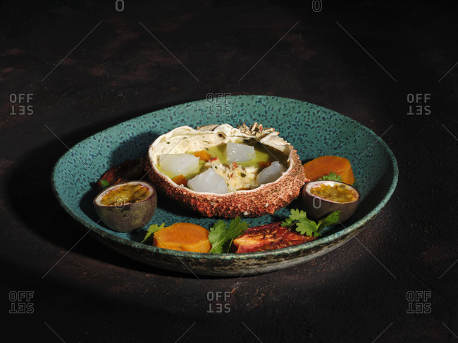 Top view of delectable ceviche served in spider crab shell with arthropod meat and fruits on plate in restaurant