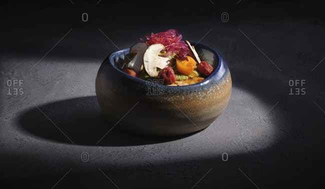 Huge bowl on cement surface full of salad with mushrooms cut in halves and vegetables