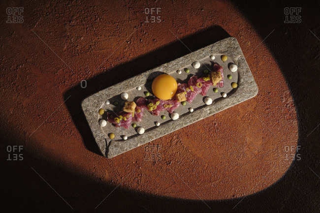 Top view of zest with meat and single egg yolk arranged on plunk in sunbeam