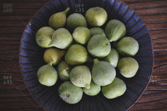 From above of blue ornamental bowl full of soft fresh figs on dark wooden table