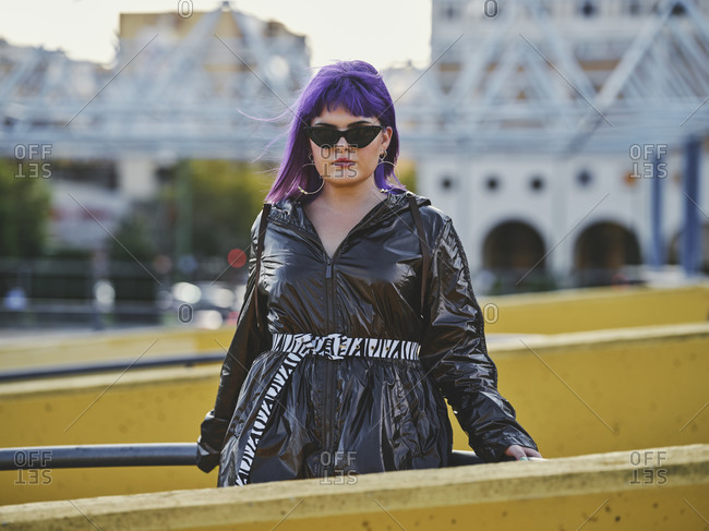Fashion confident woman with purple hairstyle in shiny black jacket and sunglasses looking at camera on city viewpoint with metal fence and yellow wall in bright day