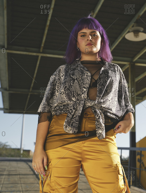 From below fashion stylish woman with purple hairstyle looking at camera with hands in pocket of yellow pants in street in bright day