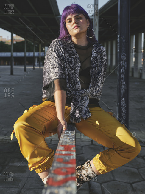 Stylish woman with bright purple hairstyle in yellow pants on metal fence in covered city station in bright day looking at camera