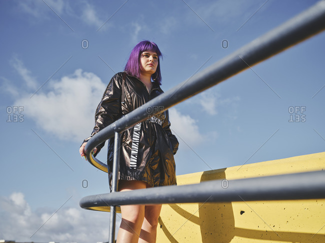 Fashion confident woman with purple hairstyle in shiny black jacket looking away putting hands in pocket on city viewpoint with metal fence and yellow wall in bright day