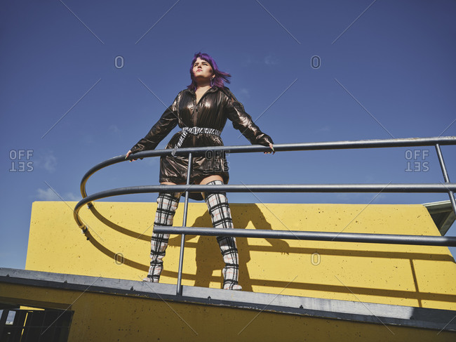 Fashion confident woman with purple hairstyle in shiny black jacket looking away in the city viewpoint with metal fence and yellow wall in bright day